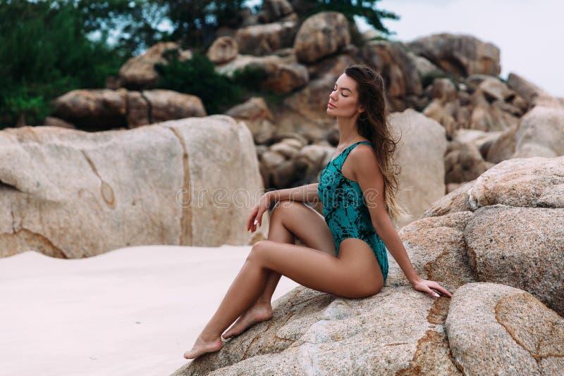 Ein sexy schönes dunkelhäutiges junges Mädchen sitzt auf einem Stein, auf einem weißen einsamen Strand und genießt den Strom des  lizenzfreie stockfotos