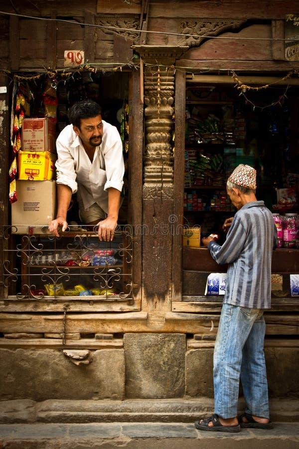 Ein Shopwächter und -kunde auf den Straßen von Kathmandu, Nepal stockfotografie