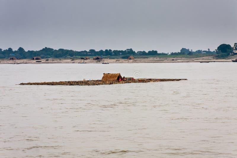 Ein sich hin- und herbewegendes Floss mit einer Familie auf dem Irrawaddy-Fluss nahe Mandalay, Myanmar lizenzfreies stockbild