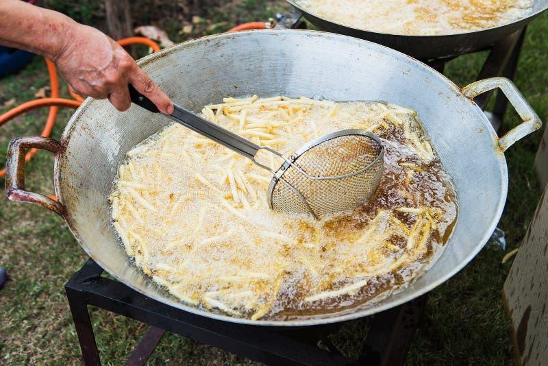 Ein Sieb voll von Pommes-Frites wird gesenkt lizenzfreie stockbilder