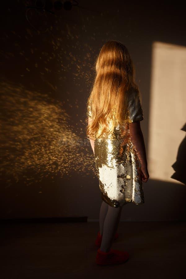 Ein siebenjähriges Mädchen, das in einem schicken Kleid verziert wird mit Goldscheinen gekleidet wird, steht im Raum, das Sonnenl stockfotos