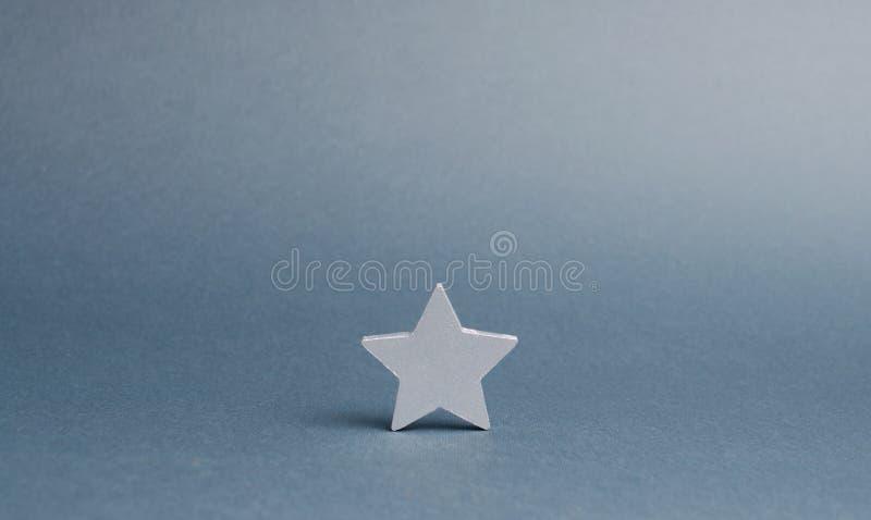 Ein silberner Stern auf einem grauen Hintergrund Das Konzept fing die Weise des Geschäfts zum Erfolg, die ersten Schritte an Das  stockfotografie