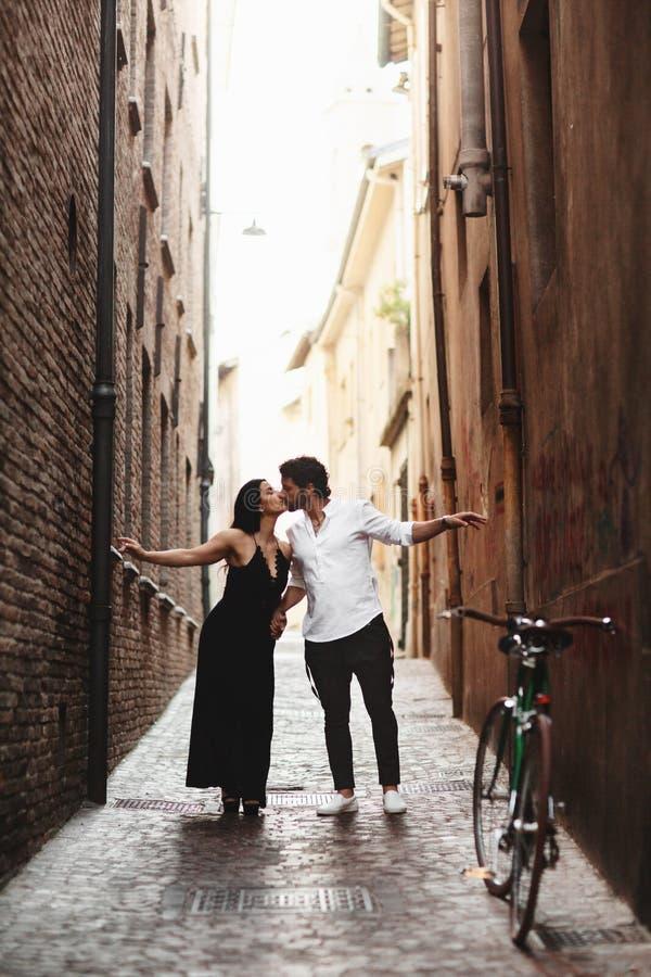 Ein sinnliches Foto von zwei jungen Leuten in einer schmalen Straße der alten Stadt Weg mit einem Fahrrad lizenzfreies stockfoto