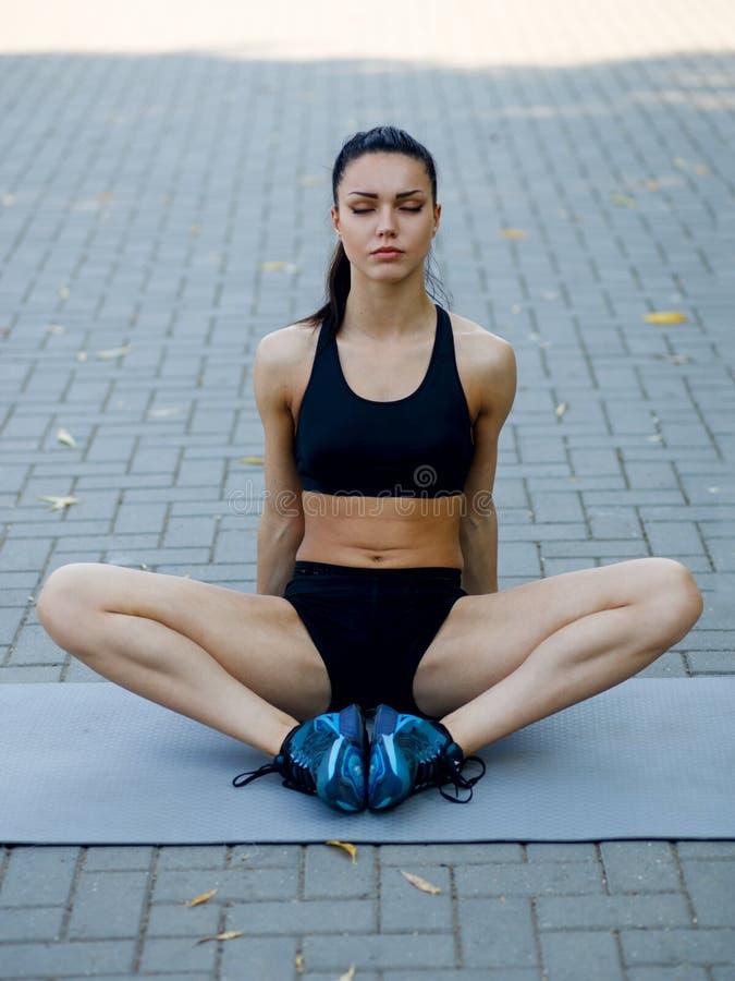 Ein Sitz, junge Frau des Athleten, die sich auf der Matte, tuend hinsetzt, Übungen draußen ausdehnend Gesunder Lebensstil stockbild