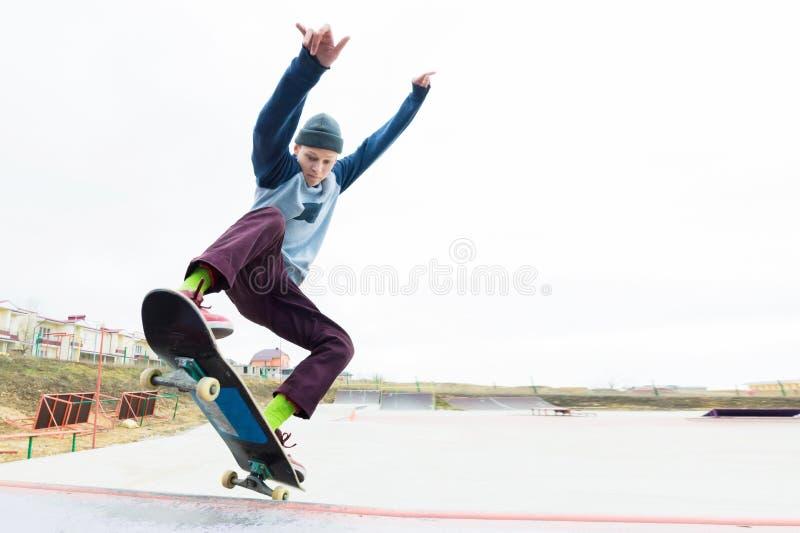 Ein Skateboardfahrerjugendlicher in einem Hut tut einen Trick mit einem Sprung auf der Rampe Ein Skateboardfahrer fliegt in die L lizenzfreies stockfoto