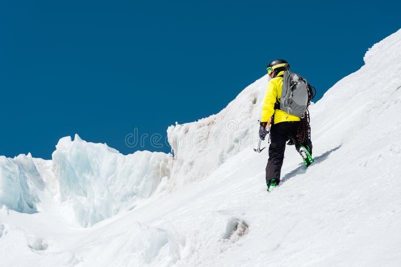 Ein Skifahrer in einem Sturzhelm und in einer Maske mit einem Rucksack steigt auf eine Steigung vor dem hintergrund des Schnees u stockfotografie