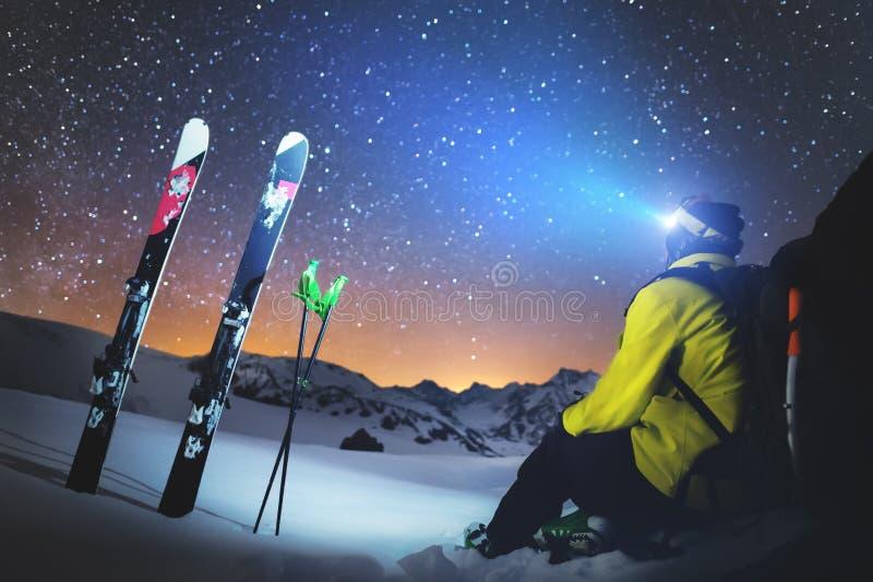 Ein Skifahrer sitzt an einem Stein in den Bergen nachts gegen einen sternenklaren Himmel nahe bei Skis und Stöcken Das Konzept de stockfotos