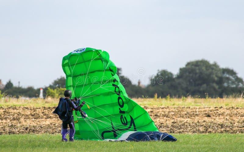 Ein Skydiver, der oben seine grüne Rutsche erfasst lizenzfreie stockfotografie