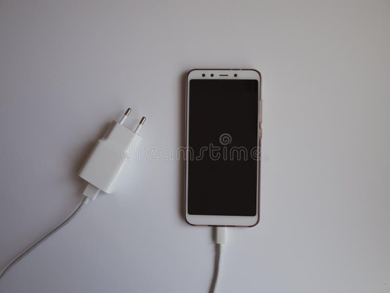 Ein Smartphone mit einem weißen USB-Kabel für die Aufladung von Draufsicht lizenzfreie stockfotos