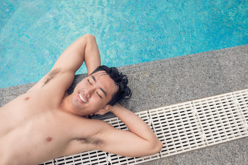 Ein Sonnenbad nehmen auf dem Poolside lizenzfreie stockbilder