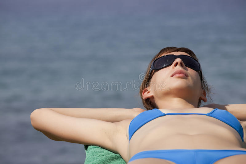 Ein Sonnenbad nehmende Frau stockfotografie