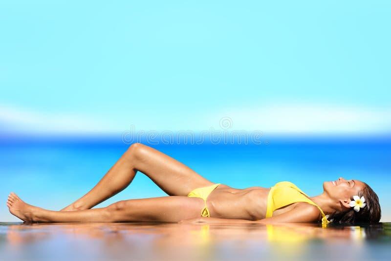 Ein Sonnenbad nehmende Frau, die unter Sonne im Luxus sich entspannt lizenzfreie stockbilder