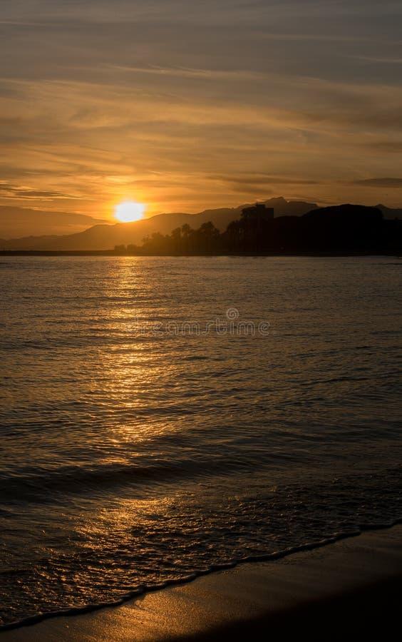 Ein Sonnenuntergang in einem Cambrils-Strand Sonnenlicht, welches das Wasser kreuzt stockbild