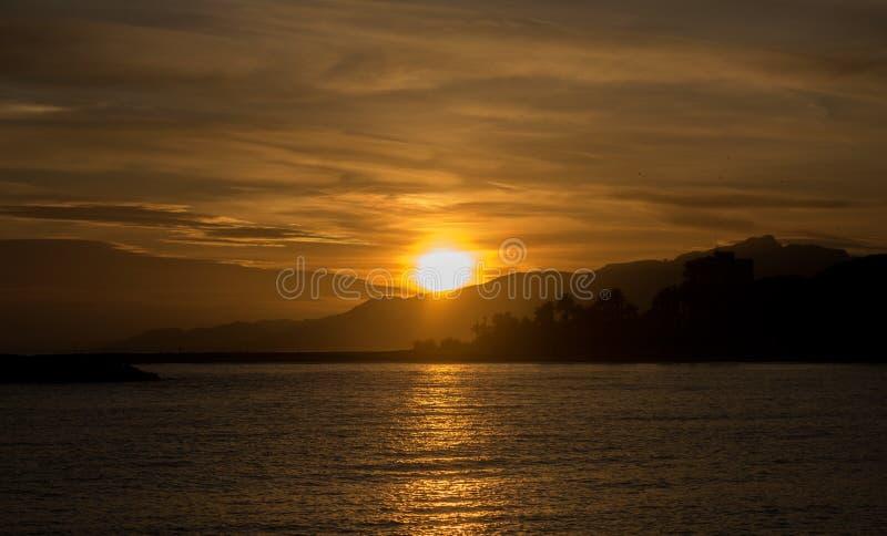 Ein Sonnenuntergang in einem Cambrils-Strand Sonnenlicht, welches das Wasser kreuzt stockfotos