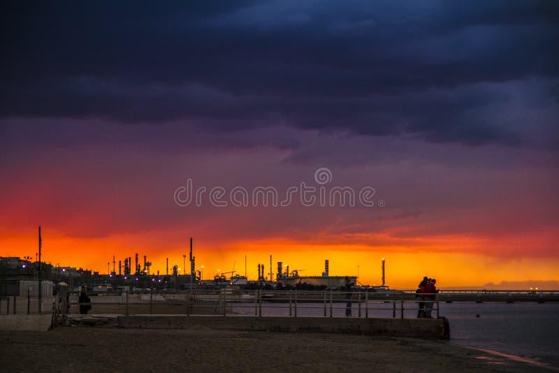 Ein Sonnenuntergang in einem Strand mit einer Raffinerie im Hintergrund stockfotografie