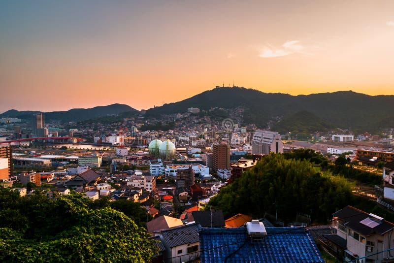 Ein Sonnenuntergang von einem Hügel in Nagasaki, Japan, mit Ansicht über die gesamte Mitte stockbild