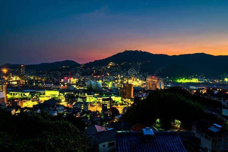 Ein Sonnenuntergang von einem Hügel in Nagasaki, Japan, mit Ansicht über die gesamte Mitte stockfotografie