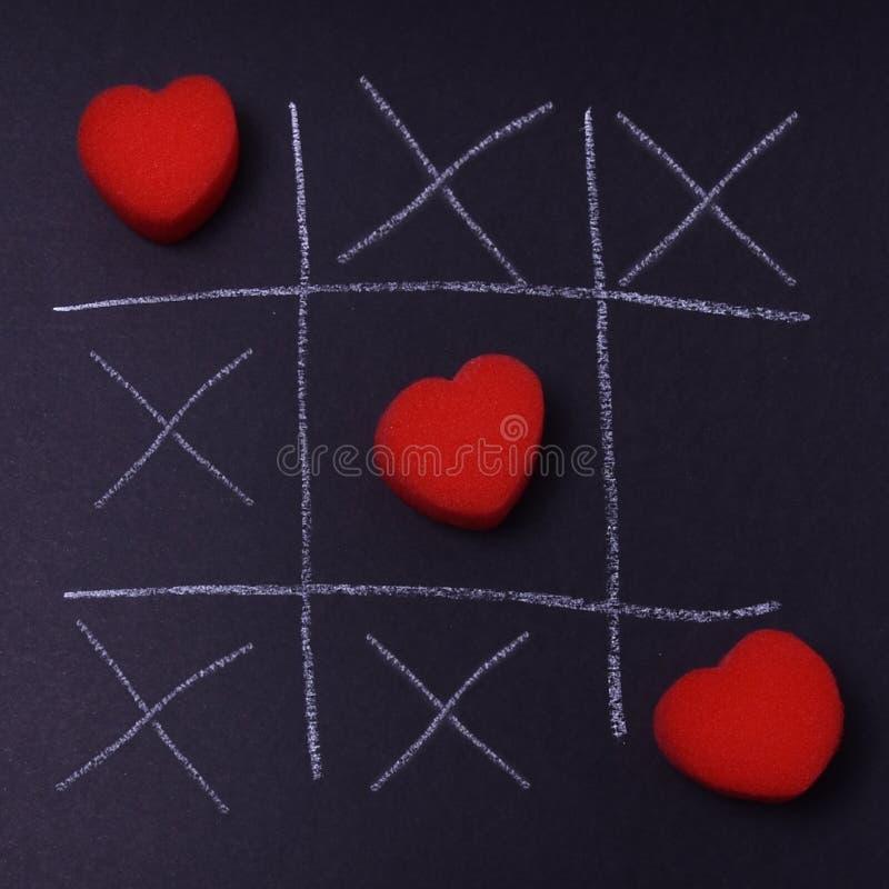 Ein Spiel der Liebe mit einer Anzeige der Spiel TIC-TAC-Zehe, jemand lizenzfreie stockfotos