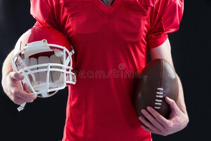 Ein Spieler des amerikanischen Fußballs, der einen Sturzhelm und einen Ball in ihren Händen nimmt stockbilder
