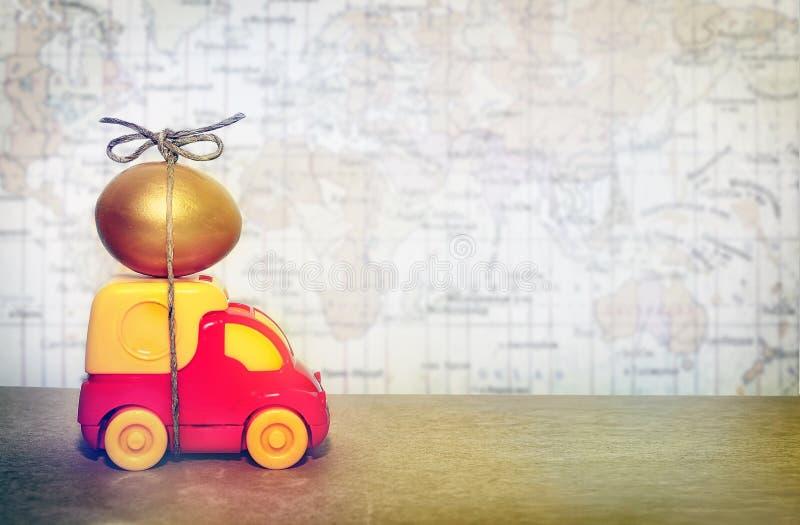 Ein Spielzeuglastwagen, der ein goldenes Ei, ein Symbol der Zuverlässigkeit der Lieferung von Postwaren transportiert stockbild
