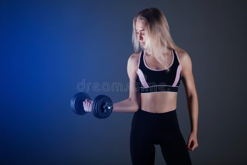Ein sportliches Mädchen hält einen Dummkopf in ihren Händen, rüttelt ein muskulöses Gegen einen dunklen Hintergrund lizenzfreies stockbild