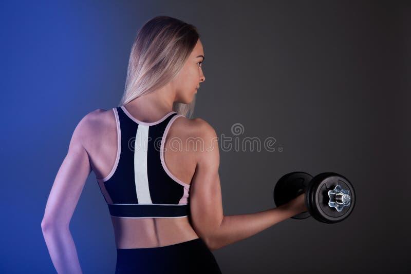 Ein sportliches Mädchen hält einen Dummkopf in ihren Händen, rüttelt ein muskulöses Gegen einen dunklen Hintergrund stockbilder
