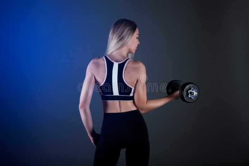 Ein sportliches Mädchen hält einen Dummkopf in ihren Händen, rüttelt ein muskulöses Gegen einen dunklen Hintergrund lizenzfreie stockfotografie