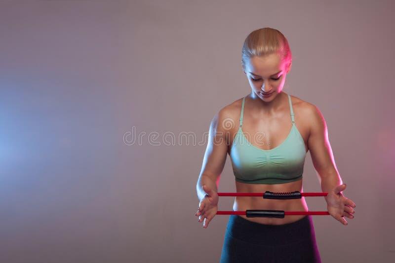 Ein sportliches Mädchen hält einen Expander für Eignung, die Muskeln sind angespannt Eignung, Sport, Training, Leute und Lebensst stockfotos