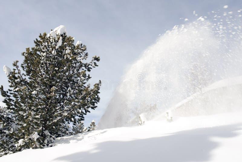 Ein Spritzen des Schnees beim Säubern des Schnees auf der Straße in den Alpen die Schweiz lizenzfreies stockbild