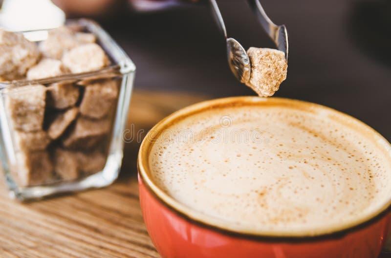 Ein Stück brauner Zucker wird der Schale mit Cappuccino hinzugefügt stockfotografie
