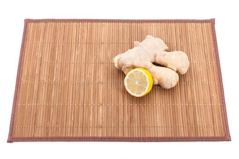 Ein Stück des Ingwers und ein Bruch der frischen Zitrone auf einer Bambusmatte stockbild