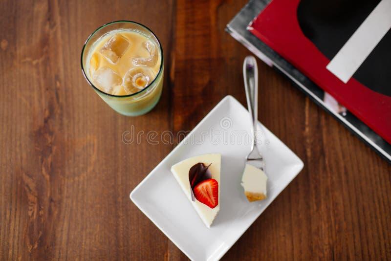 Ein Stück des Kuchens mit Erdbeere Eiskalter Kaffee lizenzfreies stockbild