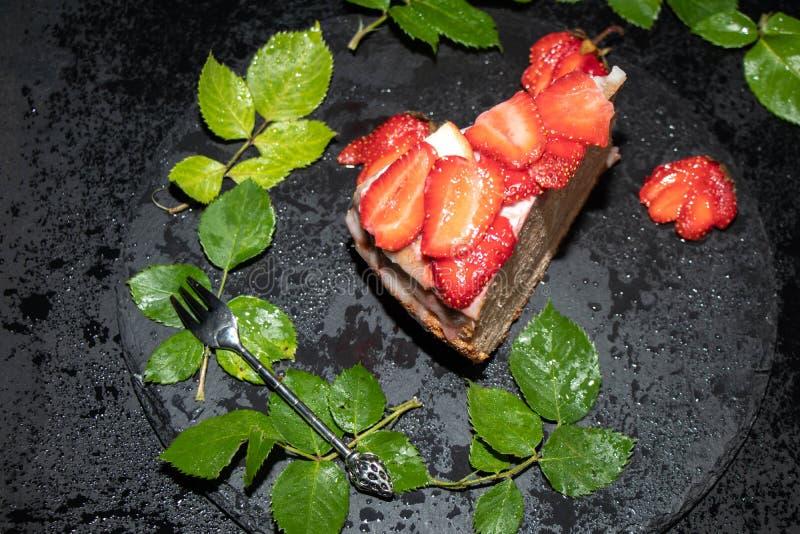 Ein Stück des Schwammkuchens mit Sahnecreme, frische Erdbeeren auf die Oberseite, Lage auf einem schwarzen Behälter stockfotografie