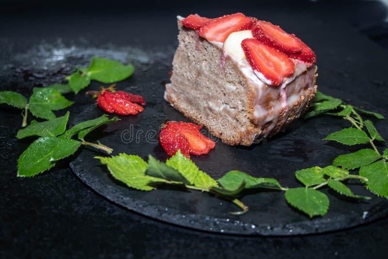 Ein Stück des Schwammkuchens mit Sahnecreme, frische Erdbeeren auf die Oberseite stockbild