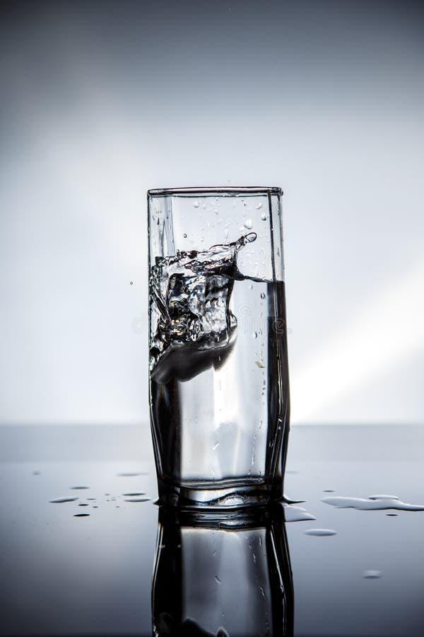 Ein Stück Eisfälle in ein Glas sauberes Trinkwasser Auf einem schönen belichteten Hintergrund stockfotografie