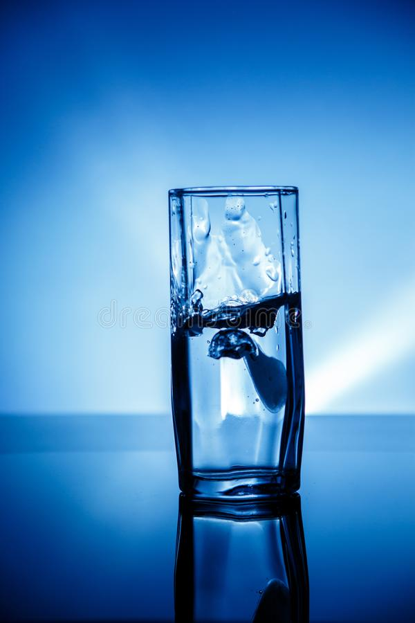 Ein Stück Eisfälle in ein Glas sauberes Trinkwasser Auf einem schönen belichteten Hintergrund lizenzfreies stockfoto
