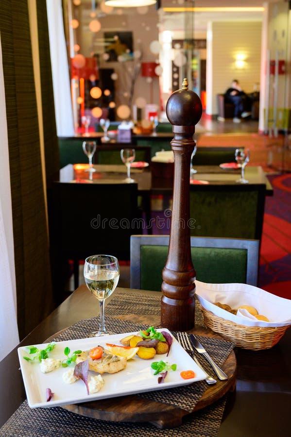 Ein Stück Fische mit Gemüse und gebratenen Kartoffeln auf einer Platte stockbilder