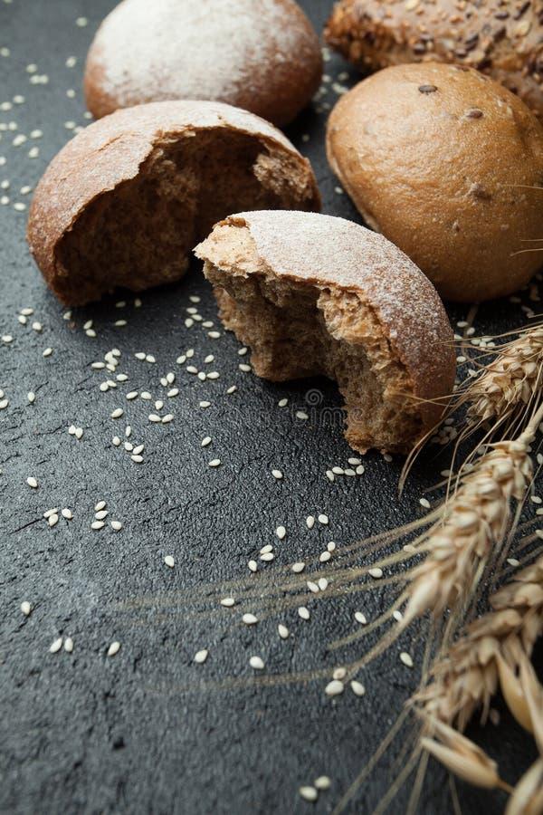 Ein Stück frisch geschnittenes Roggenbrot und Brot auf einem schwarzen Hintergrund stockfoto