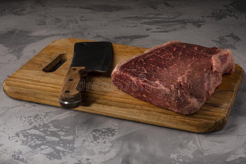 Ein Stück frisches gemarmortes Rindfleisch auf einem Schneidebrett, kochfertig lizenzfreie stockbilder