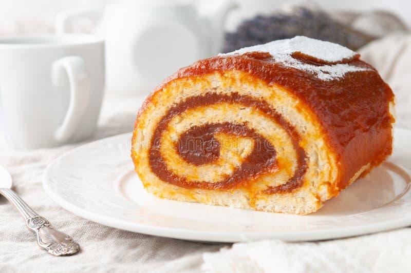 Ein Stück hausgemachter Biskuitteig mit Apfelmarmelmarmelade Auf weißer Platte Im Hintergrund ist ein weißer Teekessel und ein Sc stockfoto