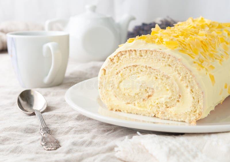 Ein Stück hausgemachtes Biskuitteig mit Banane Schokolade Auf weißer Platte Im Hintergrund ist ein weißer Teekopf und stockbilder