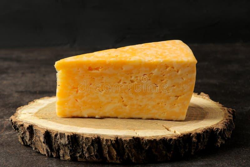 Ein Stück köstlicher gemarmorter Käse auf einem hölzernen Stand gegen einen dunklen Hintergrund Nahaufnahme stockbild