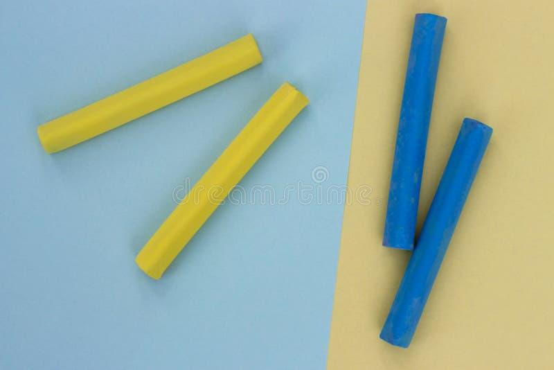 Ein Stück Kreide auf abstraktem farbigem Papier, Pastellgelb und blauem Hintergrund stockfoto