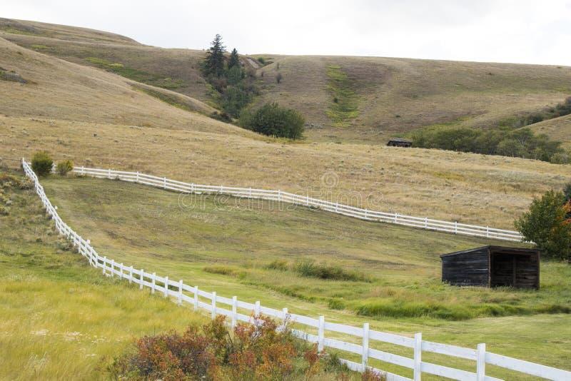 Ein Stück Land eingeschlossen mit einem weißen Zaun Alte Holz-Halle stockbilder