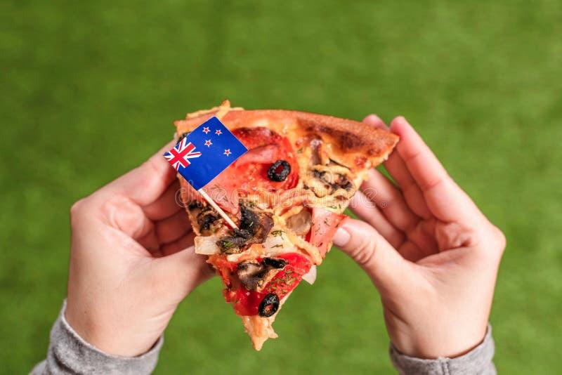 Ein Stück Pizza in weiblichen Händen mit australischer Flagge in Form eines Zahnpizzpicks. Mittagessen auf grünem Gras. austral lizenzfreies stockfoto