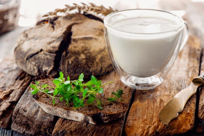 Ein Stück Roggenbrot mit einem Bündel Thymian und einem Glas/Glas der frischen Milch auf einem hölzernen Stand Das frühe Frühstüc stockbilder