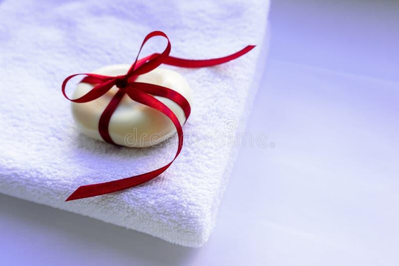 Ein Stück Seife mit einem Schleifenband in einem Bogen befestigt, liegt auf einem Handtuch. Das Konzept der Sauberkeit und der an lizenzfreie stockbilder