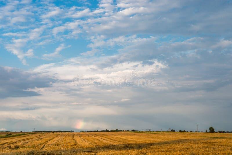 Ein Stückchen des Regenbogens über dem Feld an einem stürmischen Tag des heißen Sommers mit einem Himmel im Hintergrund stockbild