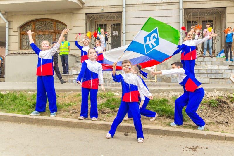 Ein Stützungskonsortium kleine Kinder in den Klagen, die dreifarbige Flagge von Russland, während der festlichen Prozession von H lizenzfreies stockbild