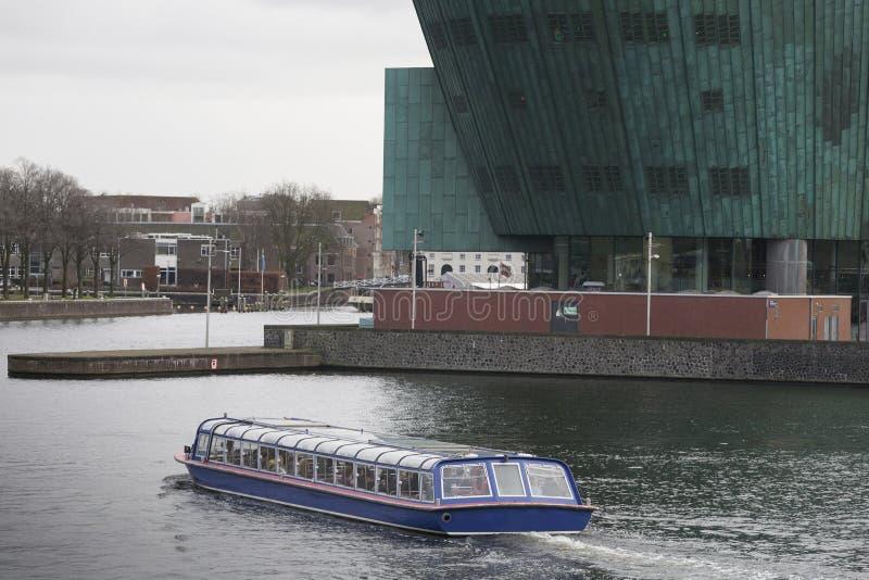 Ein Standortstandort, der Boot mit NEMO- Wissenschaftsmuseum im Hintergrund, Amsterdam die Niederlande sieht stockfotografie